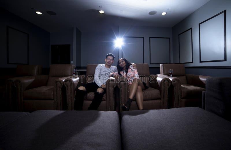 Couples interraciaux une date de home cinéma photo stock