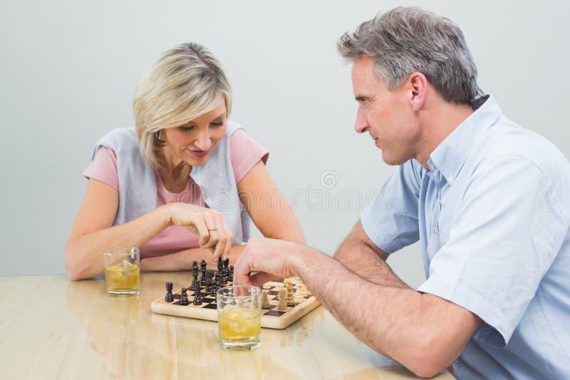 Couples jouant des échecs à la maison image libre de droits