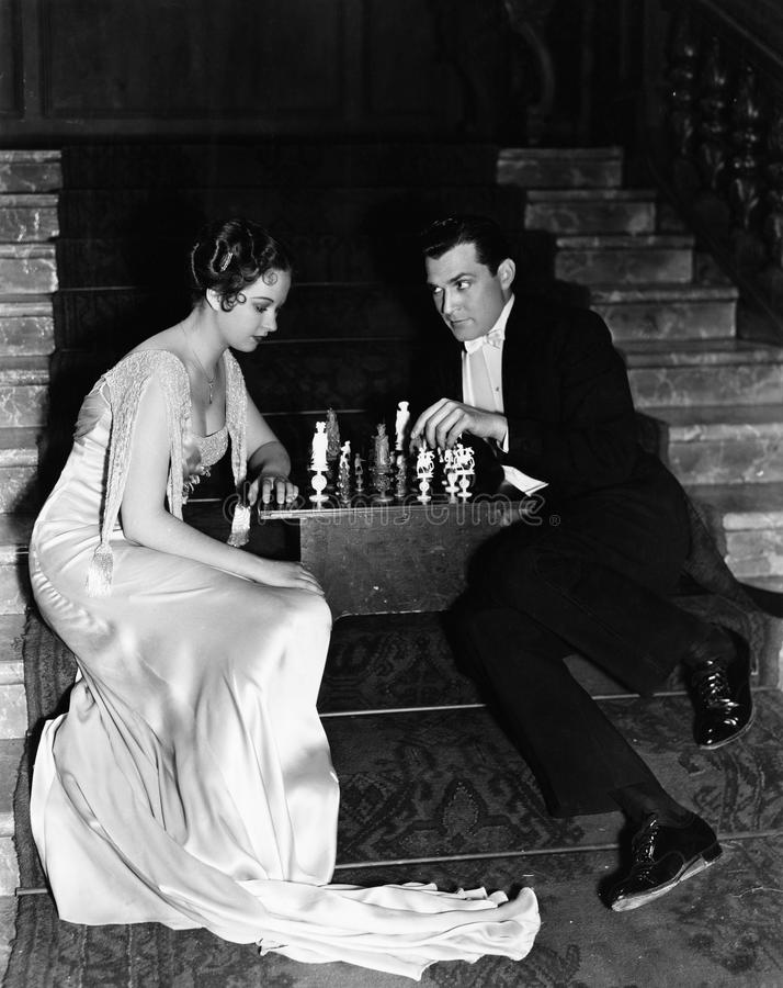 Couples jouant des échecs (toutes les personnes représentées ne sont pas plus long vivantes et aucun domaine n'existe Garanties d photos libres de droits