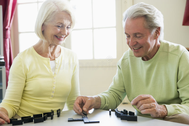 Couples jouant des dominos dans le sourire de salle de séjour photo libre de droits