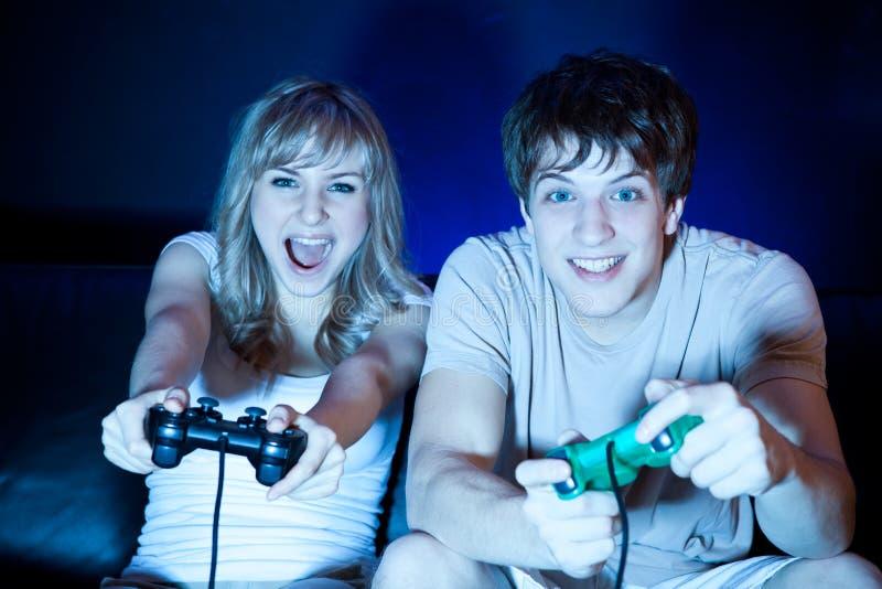 Couples jouant des jeux vidéo images stock