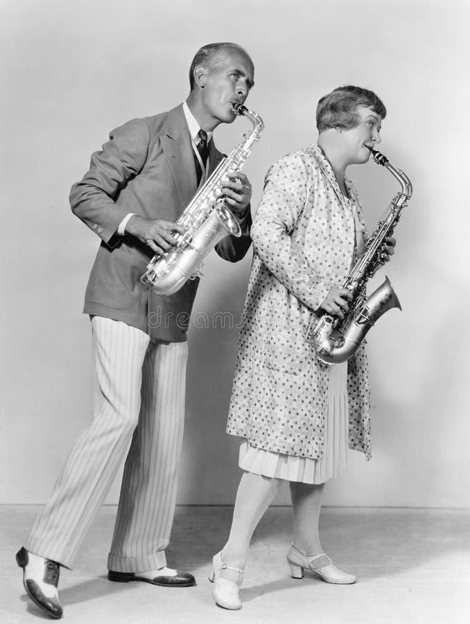 Couples jouant des saxophones ensemble (toutes les personnes représentées ne sont pas plus long vivantes et aucun domaine n'exist images stock
