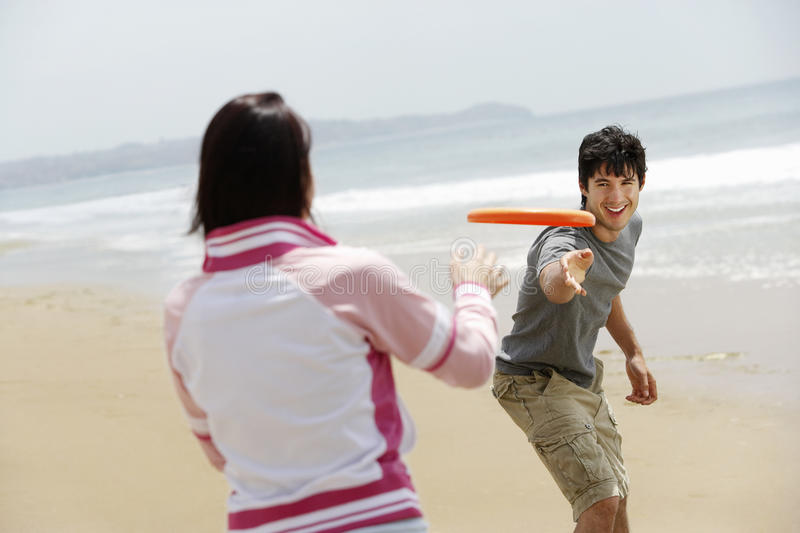 Couples jouant le frisbee sur la plage photo stock