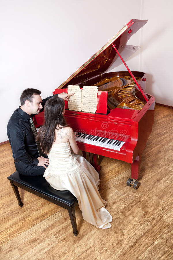 Couples jouant le piano rouge photographie stock libre de droits