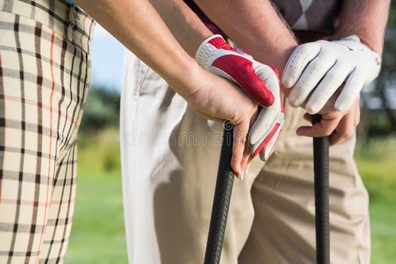Couples jouants au golf se tenant tenants leurs clubs photos libres de droits