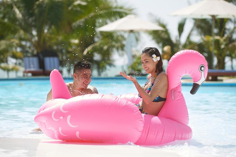 Couples joyeux dans la piscine photographie stock libre de droits