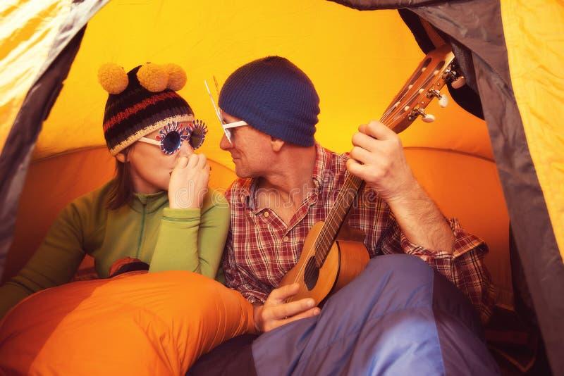 Couples joyeux dans le voyage jouant l'ukulélé photo stock