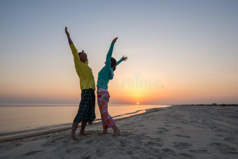 Couples joyeux des voyageurs ayant l'amusement sur la plage image libre de droits