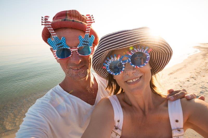 Couples joyeux des voyageurs dans des lunettes de soleil drôles prenant le selfie photo stock