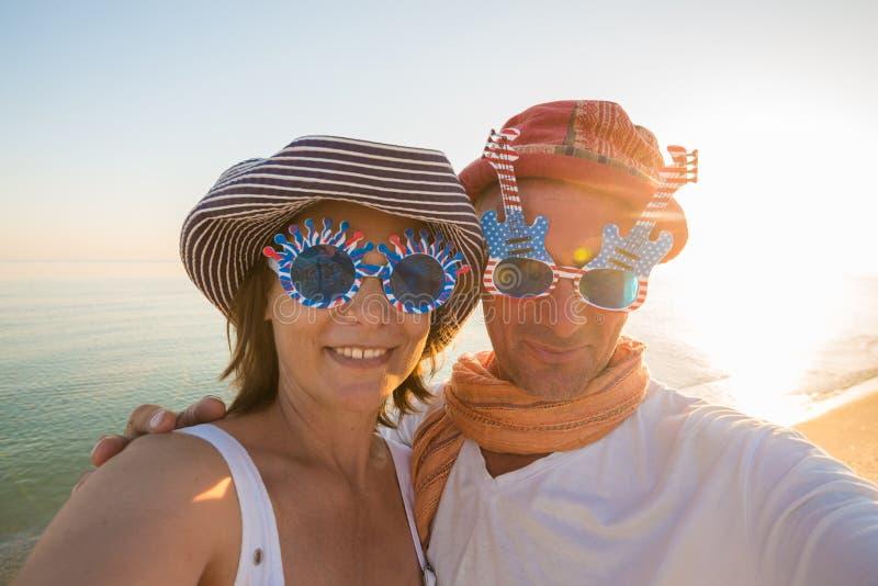 Couples joyeux des voyageurs, dans des lunettes de soleil drôles, prenant le selfie photo stock