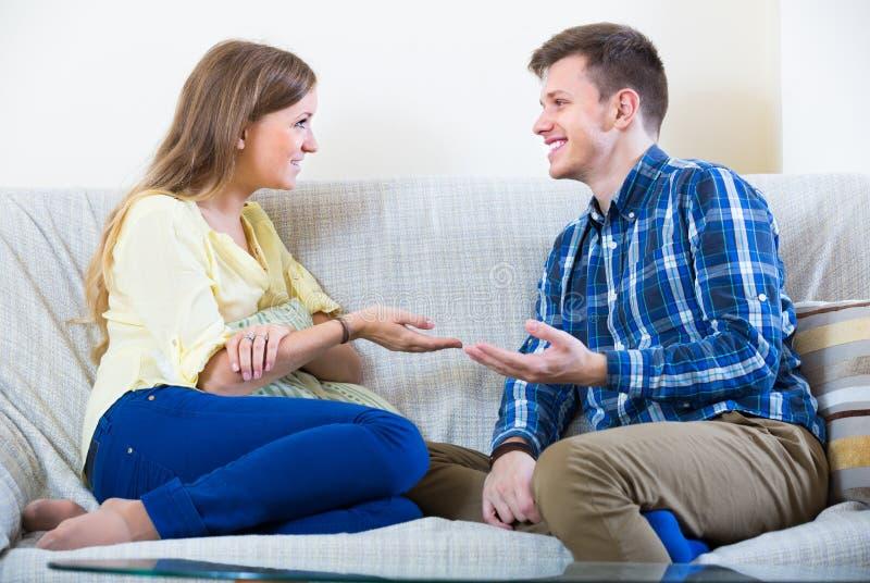 Couples joyeux parlant à la maison photographie stock