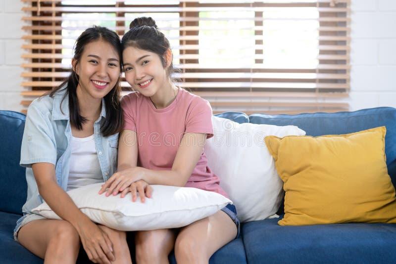 Couples lesbiens de jeune Asiatique heureux attirant souriant et regardant la cam?ra se reposant sur le divan bleu ensemble dans  photos libres de droits