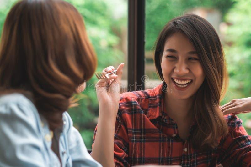 Couples lesbiens de lgbt de femmes asiatiques reposant chaque côté mangeant un plat des spaghetti et des pommes frites italiens d photographie stock libre de droits