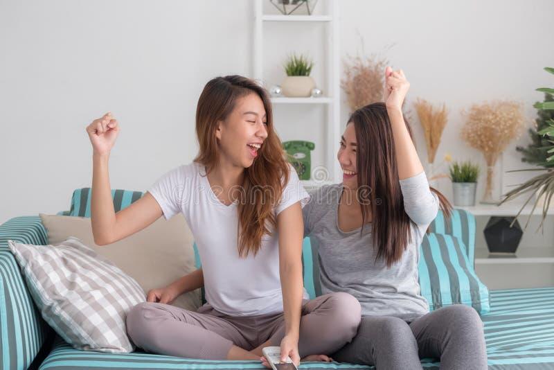 Couples lesbiens de lgbt de l'Asie tenant l'exposition de TV et le che de observation à distance photographie stock libre de droits