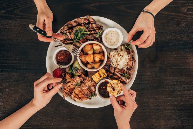 couples lesbiens mangeant des biftecks de boeuf et des légumes grillés photos stock