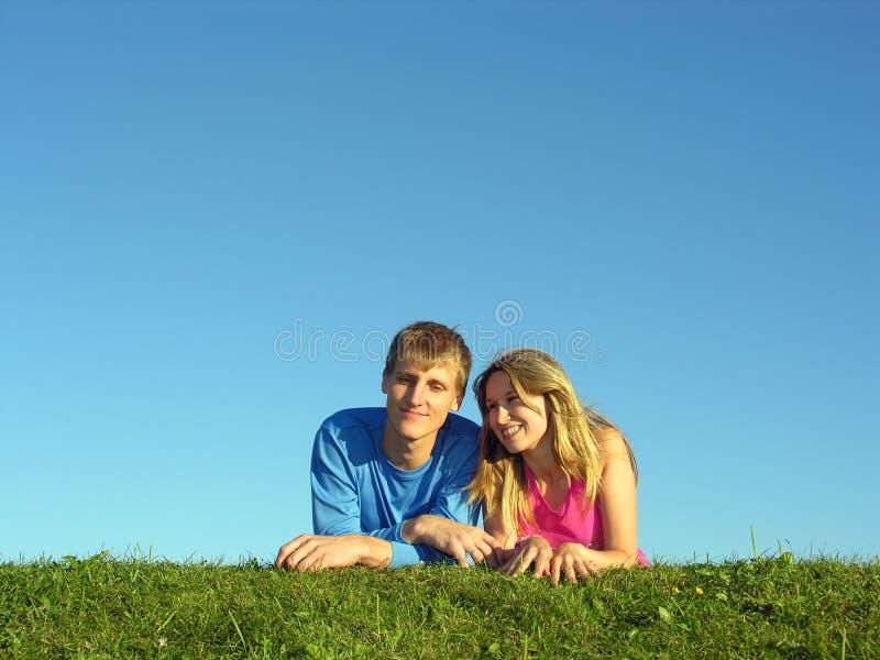Couples lie on grass. Blue sky