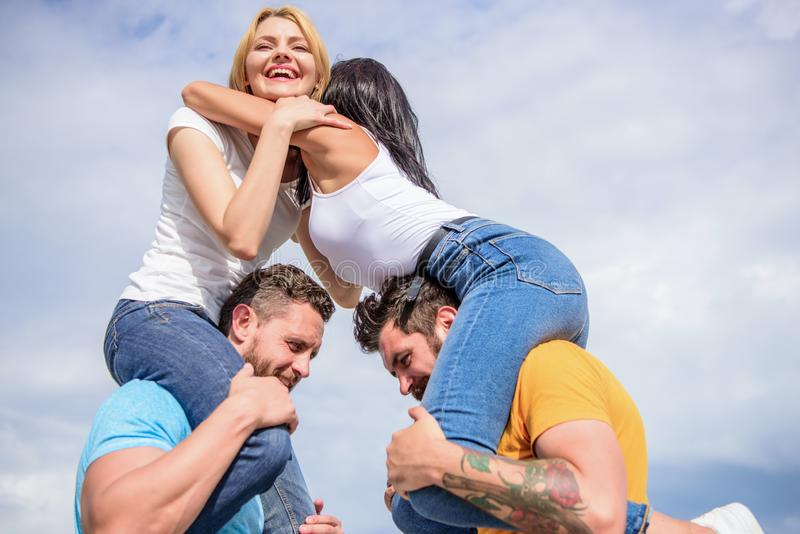 Couples in love having fun. Men carry girlfriends on shoulders. Summer vacation and fun. Couples on double date. Inviting another couple to join. Friendship of royalty free stock photos