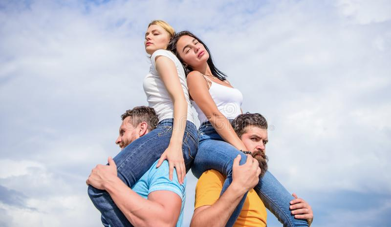 Couples in love having fun. Men carry girlfriends on shoulders. Summer vacation and fun. Couples on double date. Inviting another couple to join. Twice fun on royalty free stock image