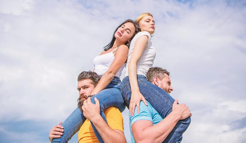 Couples in love having fun. Men carry girlfriends on shoulders. Summer vacation and fun. Couples on double date. Inviting another couple to join. Twice fun on stock photos