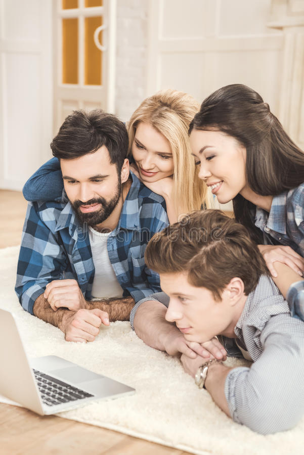 Couples lying on floor and having fun. Two young couples lying on floor, having fun and using laptop stock photos