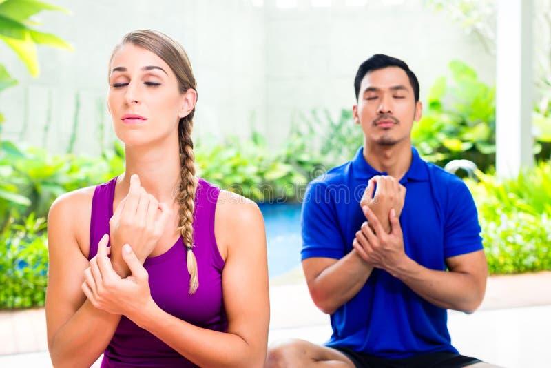 Couples mélangés à la formation de yoga en Asie tropicale photo libre de droits