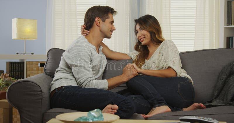 Couples mélangés affectueux parlant sur le divan images libres de droits