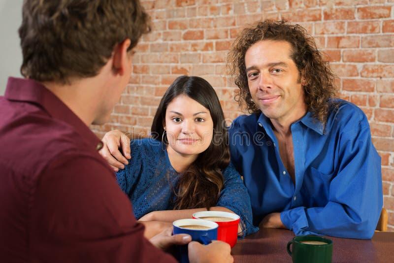 Couples mélangés mignons en café photo libre de droits