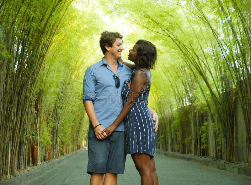 Couples mélangés tendres d'appartenance ethnique caressant dehors avec la femme afro-américaine noire attirante et l'ami caucasie photographie stock libre de droits