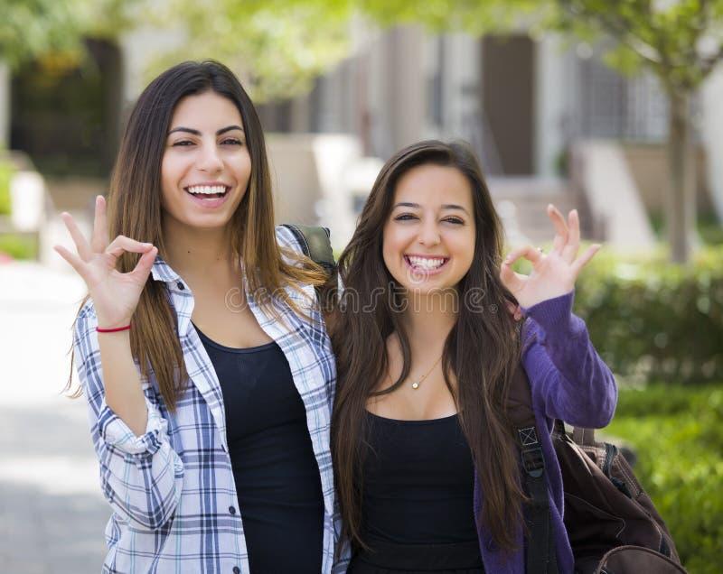 Couples mêmes sexes heureux de métis sur le campus d'école avec le signe correct image stock