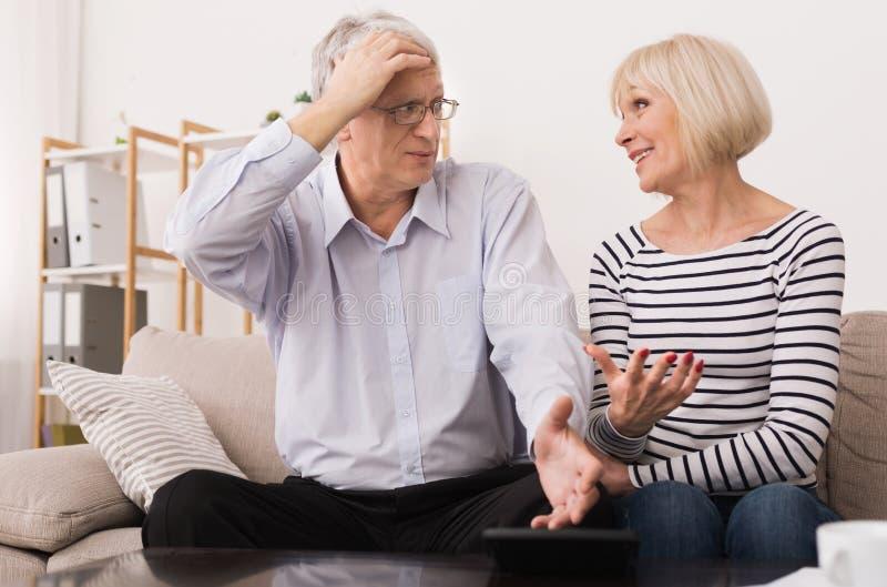 Couples mûrs calculant des factures, discutant l'économie ménagère images stock