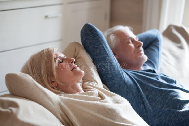 Couples mûrs calmes détendant sur le sofa ayant le petit somme de jour ensemble photos stock