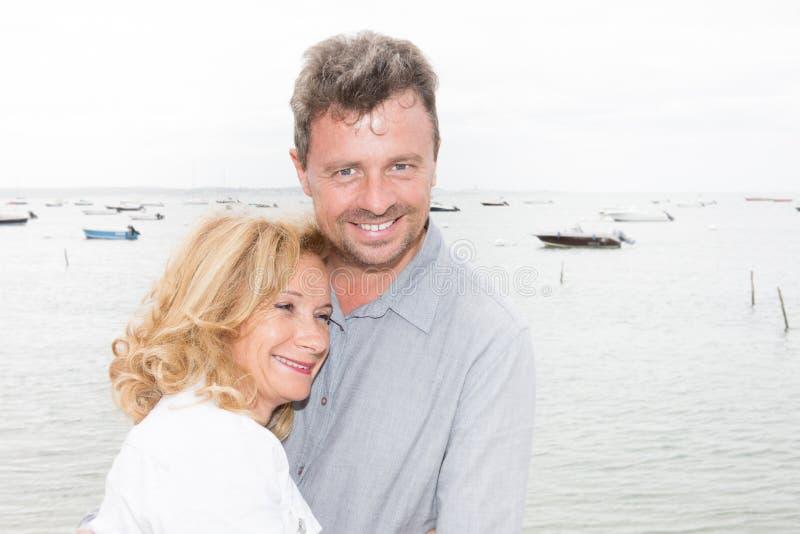 Couples mûrs dans les vacances près de la mer et du bateau de côte photographie stock