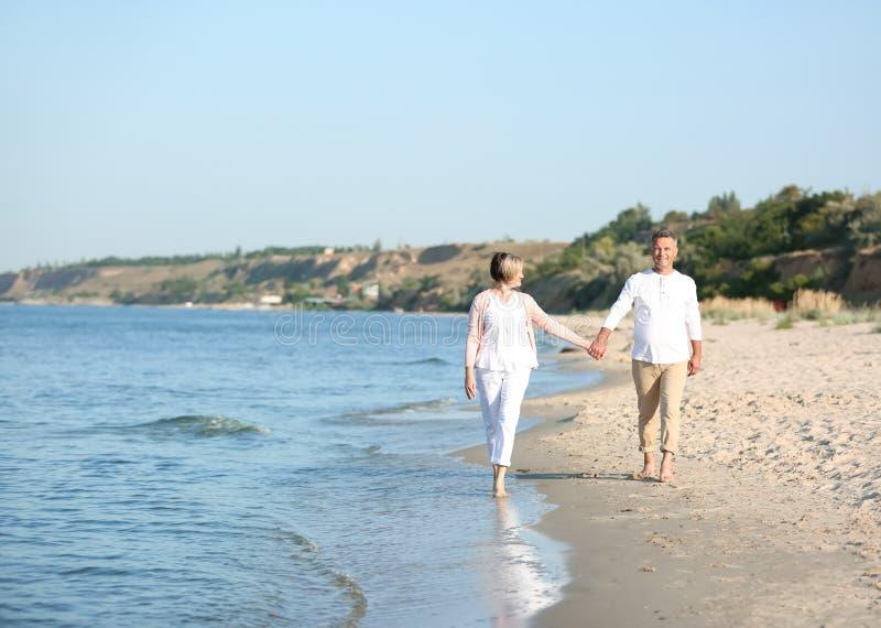 Couples mûrs heureux marchant à la plage images stock