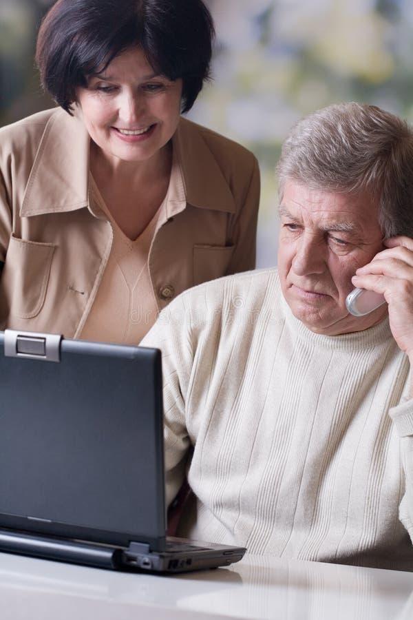 Couples mûrs heureux travaillant sur l'ordinateur portatif images libres de droits