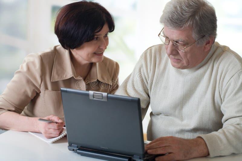 Couples mûrs heureux travaillant sur l'ordinateur portatif image libre de droits