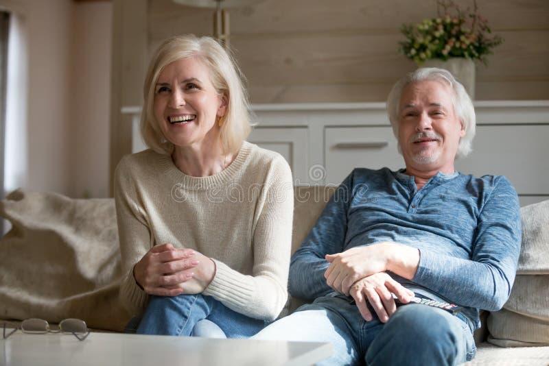 Couples mûrs heureux TV de observation riante ensemble dans le salon photo stock