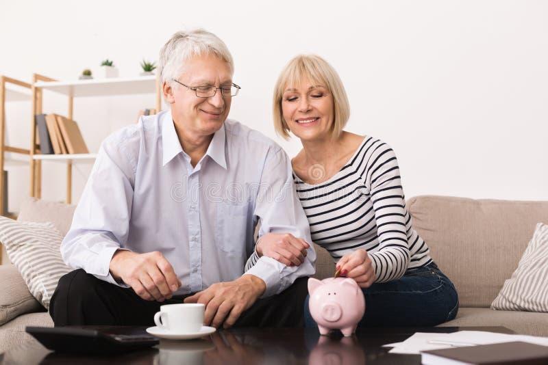Couples mûrs mettant l'argent dans la tirelire à la maison image libre de droits