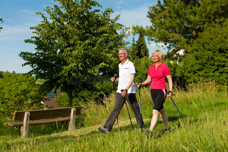 Couples mûrs ou aînés heureux faisant la marche de Nordic images stock