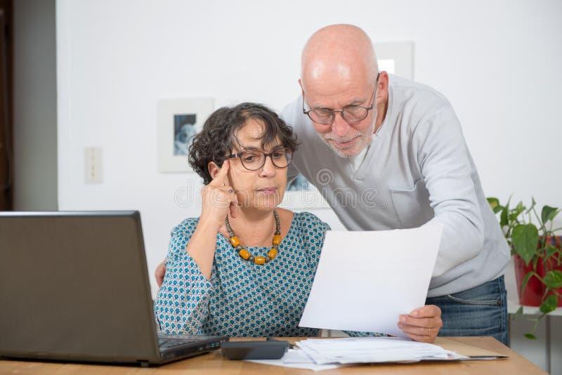 Couples mûrs payant leurs factures avec l'ordinateur portable à la maison image stock