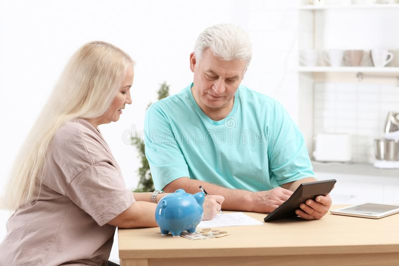 Couples mûrs pensant au-dessus du paiement de pension photos libres de droits