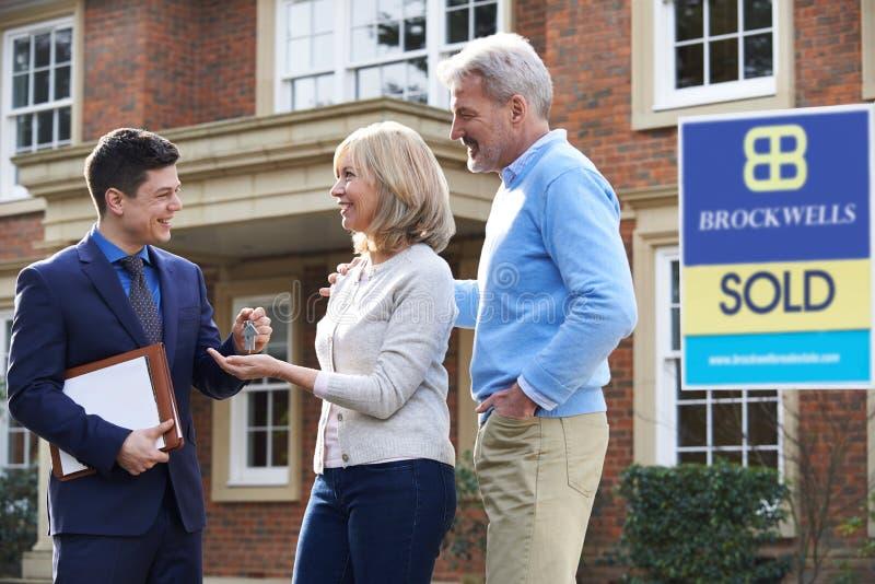 Couples mûrs rassemblant des clés à la nouvelle maison de l'agent immobilier images stock