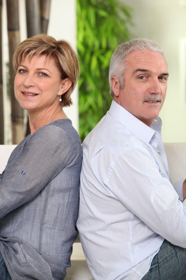 Couples mûrs se reposant de nouveau au dos photos stock