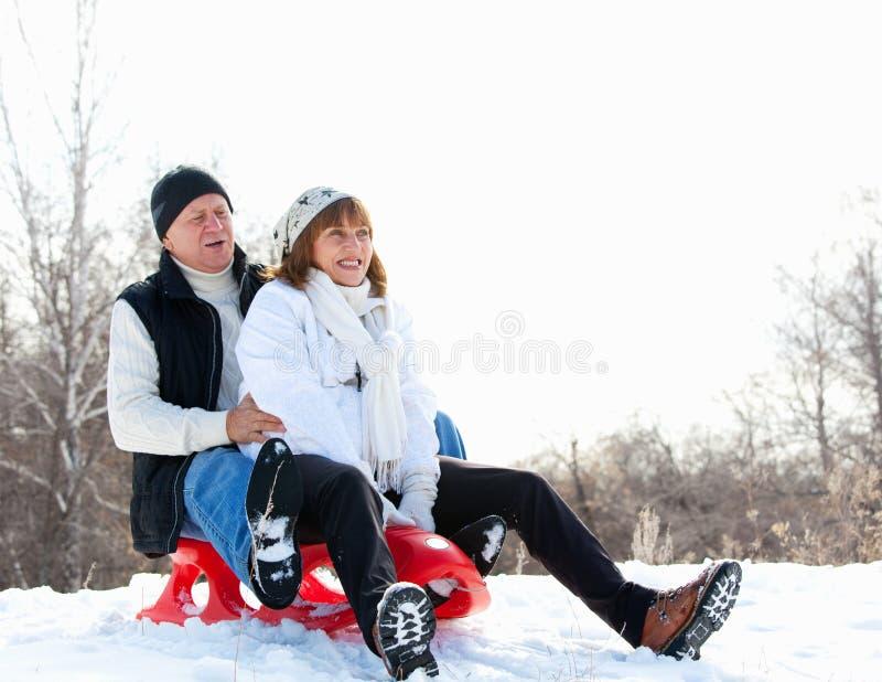 Couples mûrs sledding photographie stock libre de droits