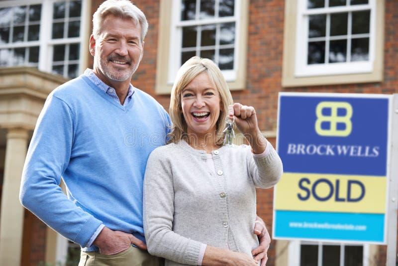 Couples mûrs tenant des clés sur la nouvelle maison se tenant prêt le signe vendu image stock