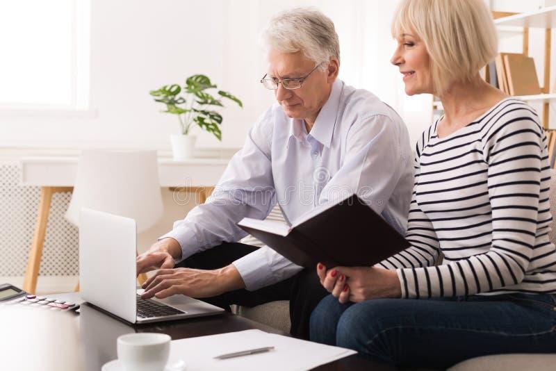 Couples mûrs vérifiant des finances domestiques utilisant l'ordinateur portable image libre de droits