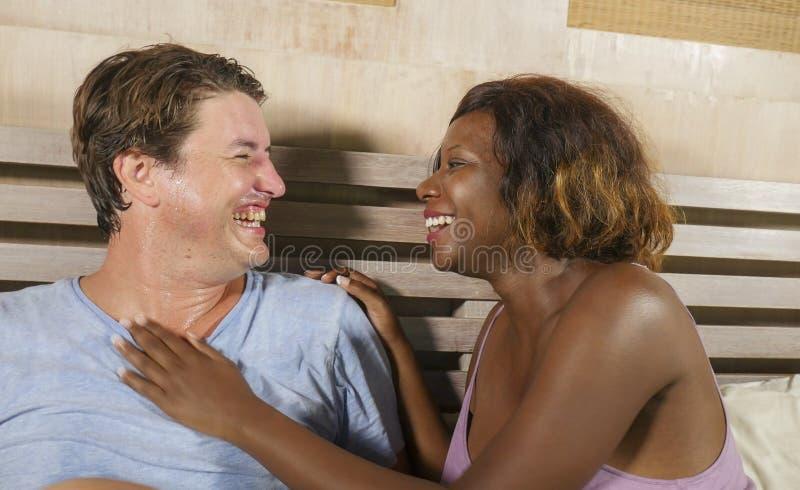 Couples m?lang?s d'appartenance ethnique dans l'amour caressant ensemble ? la maison dans le lit avec la beaux femme et Caucasien photo libre de droits