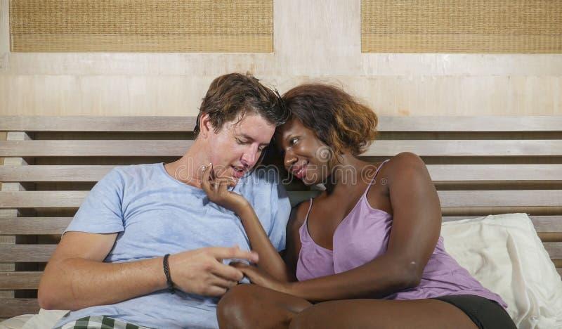 Couples m?lang?s d'appartenance ethnique dans l'amour caressant ensemble ? la maison dans le lit avec la beaux femme et Caucasien image stock