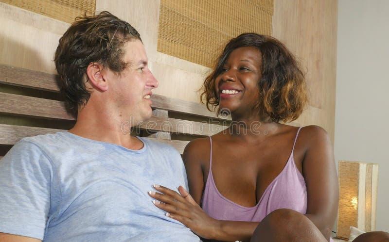 Couples m?lang?s d'appartenance ethnique dans l'amour caressant ensemble ? la maison dans le lit avec la beaux femme et Caucasien photographie stock