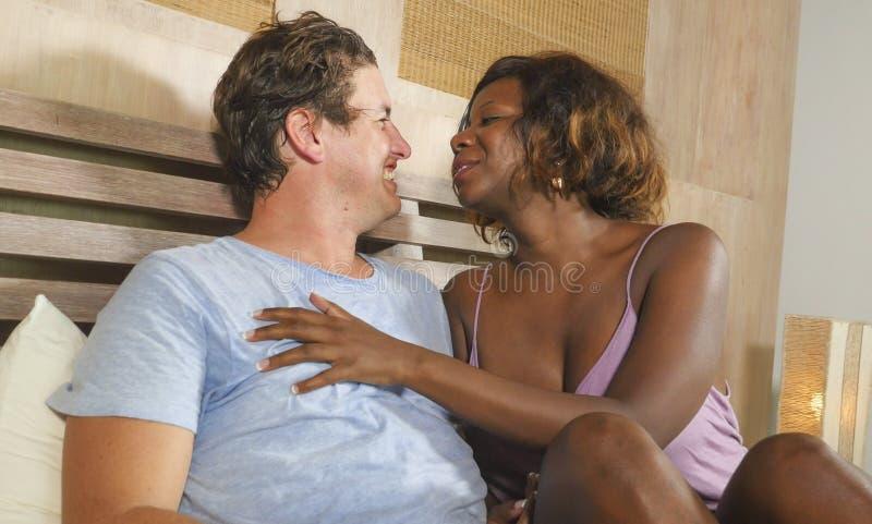 Couples m?lang?s d'appartenance ethnique dans l'amour caressant ensemble ? la maison dans le lit avec la beaux femme et Caucasien image libre de droits