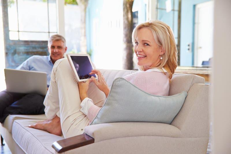 Couples mûrs à la maison dans le salon utilisant des dispositifs de Digital photographie stock